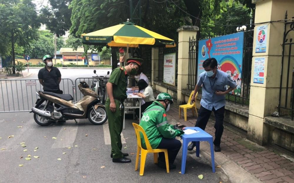 Lực lượng chức năng quận Thanh Xuân lập biên bản xử phạt cá nhân ra đường không lý do. (Ảnh: Hữu Duyên)