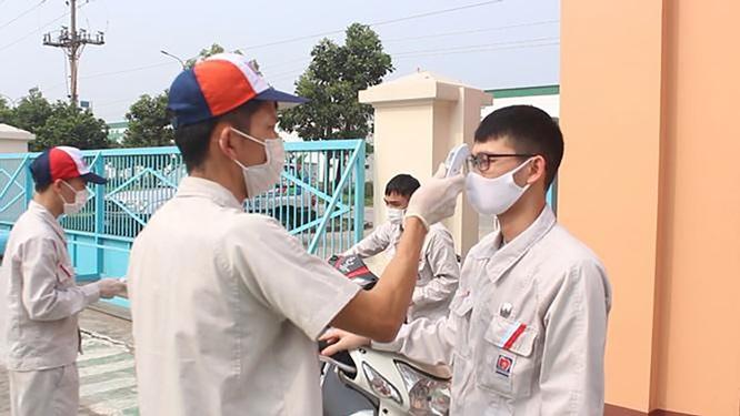 Công nhân được đo thân nhiệt trước khi vào làm việc tại Công ty TNHH Nippon Paint Việt Nam (Khu công nghiệp Quang Minh, Hà Nội)