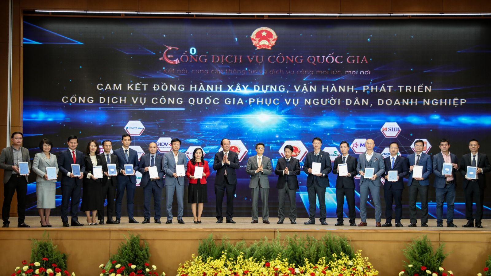Phó Tổng giám đốc VPBank Đinh Văn Nho (thứ 5 từ trái sang) và các doanh nghiệp ký cam kết đồng hành xây dựng, phát triển Cổng Dịch vụ công quốc gia. (Ảnh: Minh Sơn/Vietnam+)
