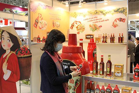 Các đối tác nước ngoài tìm hiểu về nông sản và thực phẩm tại gian hàng quốc gia Việt Nam.