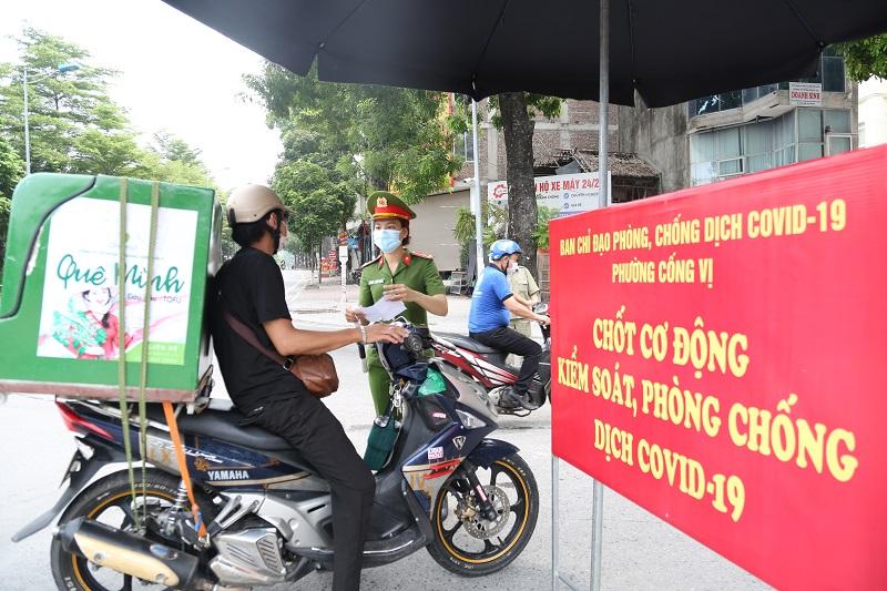 Lực lượng chức năng phường Cống Vị, quận Ba Đình kiểm tra giấy tờ tùy thân tại chốt kiểm soát dịch Covid-19 trên phố Đội Cấn.