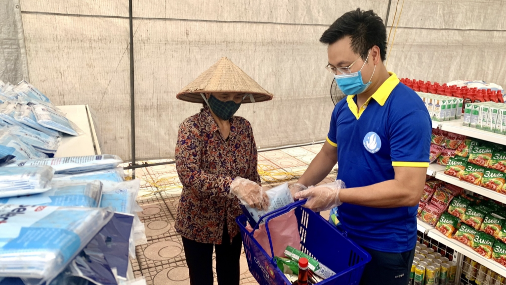 Đồng chí Trần Quang Hưng, Phó Bí thư Thành đoàn, Chủ tịch Hội Sinh viên thành phố Hà Nội hỗ trợ người dân mua sắm tại Siêu thị mini 0 đồng