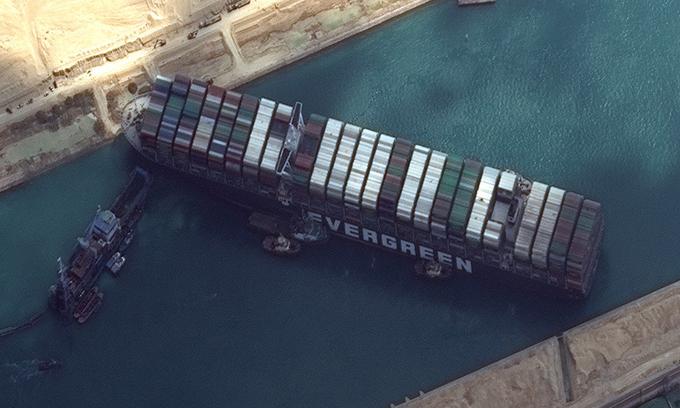 Tàu Ever Given chắn ngang kênh Suez nhìn từ vệ tinh, phía bên trái là con tàu nạo vét cát. Ảnh: AFP