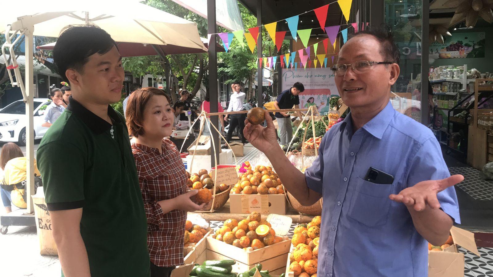 Ông Nguyễn Quang Đông – nông dân sản xuất nông sản hữu cơ đang giới thiệu sản phẩm với khách hàng.
