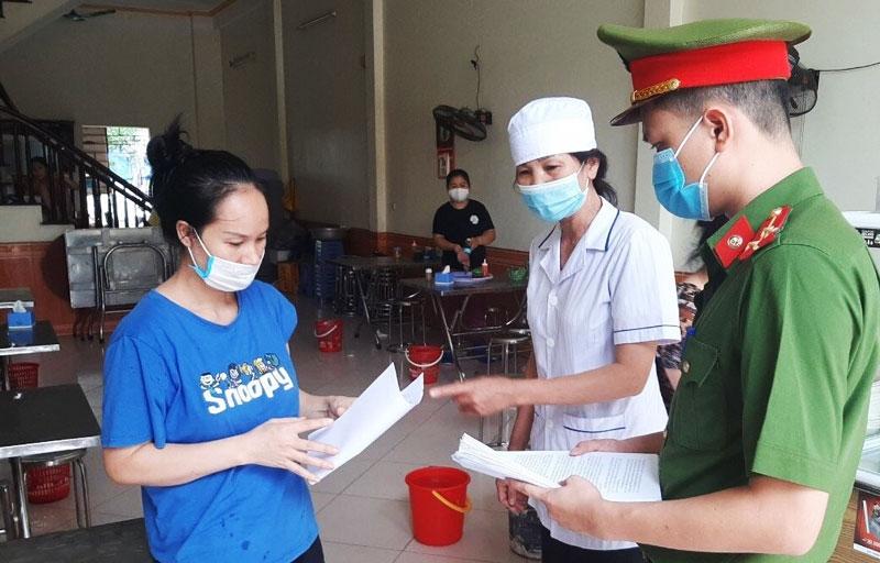 Lực lượng chức năng thị trấn Tây Đằng (huyện Ba Vì) tổ chức cho các hộ kinh doanh trên địa bàn ký cam kết phòng, chống dịch Covid-19