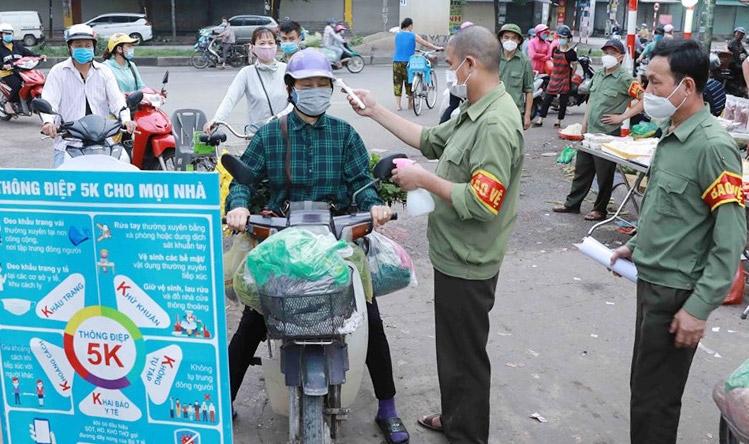 Kiểm tra thân nhiệt cho người dân tại chợ đầu mối Minh Khai, quận Bắc Từ Liêm (Ảnh: Vũ Sinh)