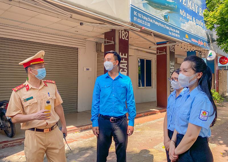 Phó Bí thư Thường trực Thành đoàn Nguyễn Đức Tiến trao tặng nước mát đến chiến sĩ công an.