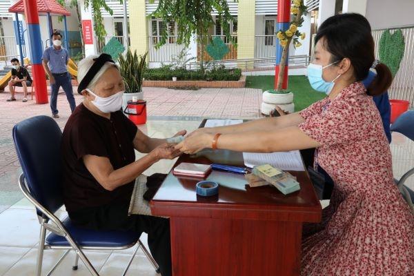 Cán bộ xã Tiền Yên, huyện Hoài Đức chi trả kinh phí hỗ trợ đặc thù cho đối tượng thụ hưởng.
