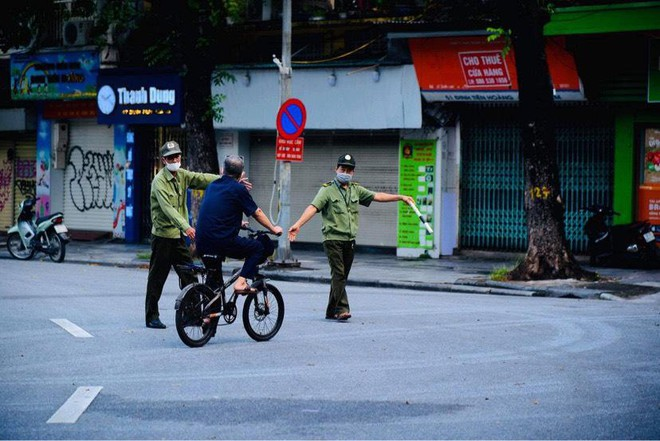 Lực lượng chức năng nhắc nhở người dân khi ra khỏi nhà vì lý do không chính đáng sáng 24-7 tại Hà Nội