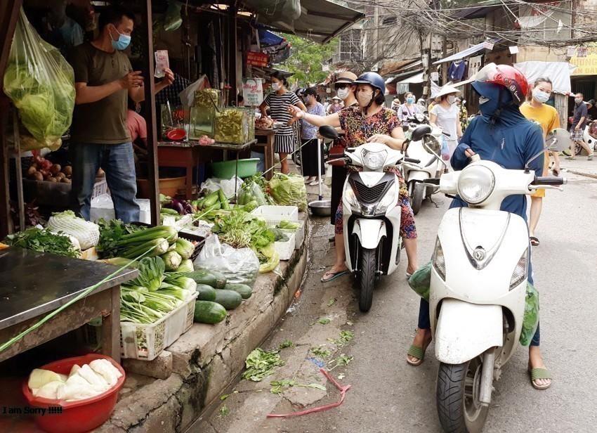 Người tiêu dùng mua rau xanh tại chợ Nam Đồng ( Đống Đa)