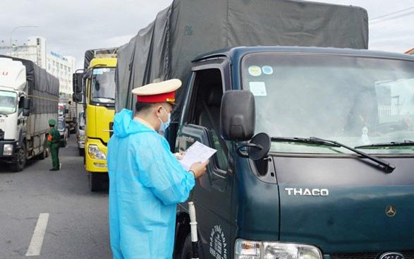 Lực lượng chức năng kiểm tra thông tin của lái xe tại một chốt kiểm soát dịch Covid-19.