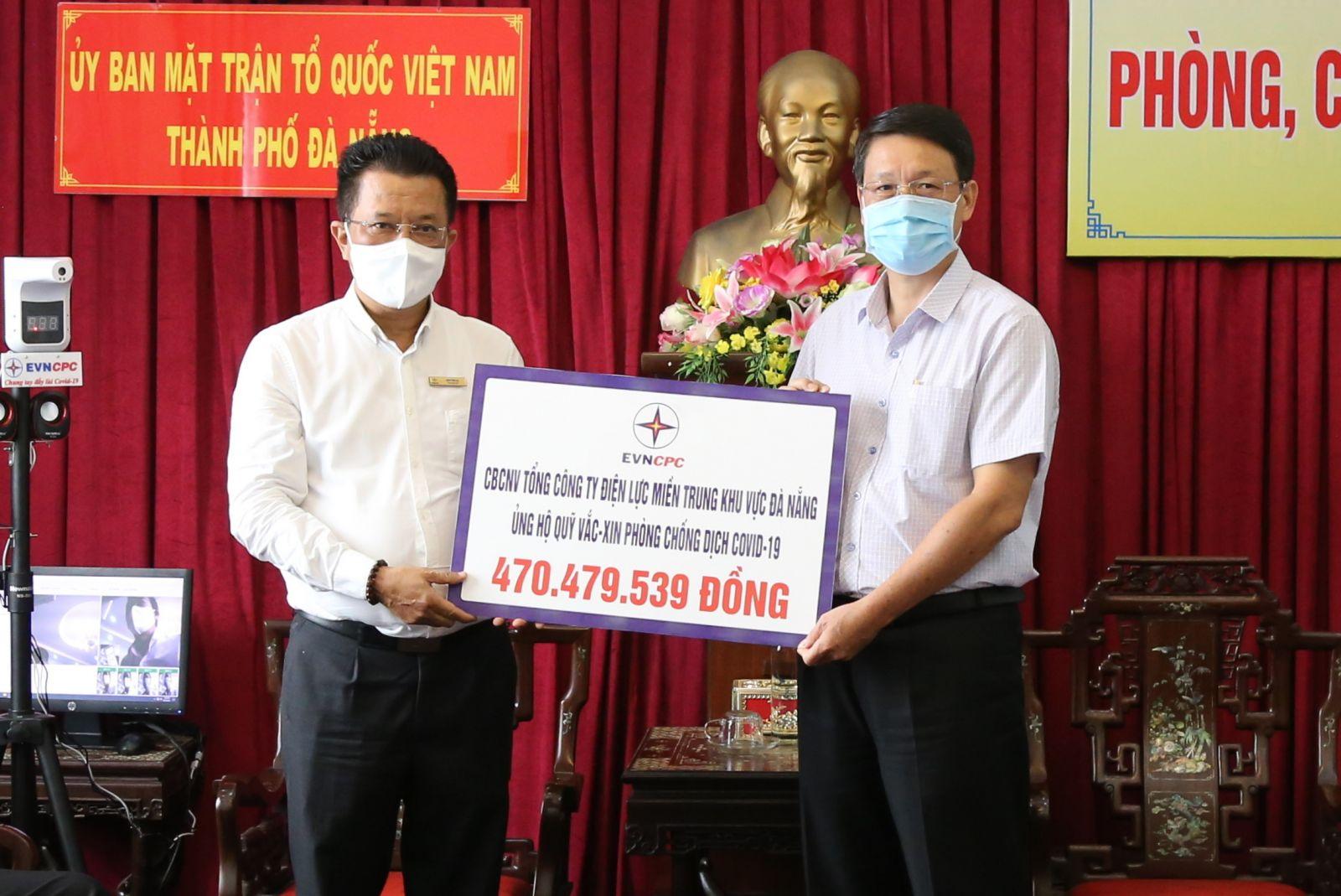 Tổng giám đốc EVNCPC Ngô Tấn Cư (bên trái) trao bảng tượng trưng kinh phí hỗ trợ mua vắc xin và trao tặng 15 máy đo thân nhiệt tự động tổng trị giá 150 triệu đồng cho Ủy ban MTTQ Việt Nam TP. Đà Nẵng.