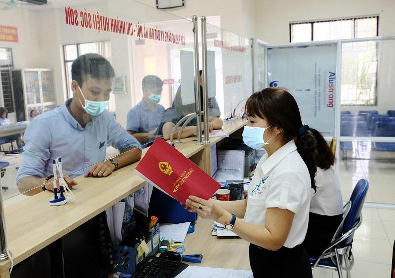 Giải quyết thủ tục hành chính cho người dân tại UBND huyện Sóc Sơn. Ảnh: Phạm Hùng